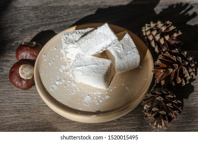 Delicious white turkish delight on wooden dish sprinkled with icing sugar like snow. Oriental pieces of flavoured sweets next to pine cones and chestnut nuts. Winter Christmas dessert in the sunshine.