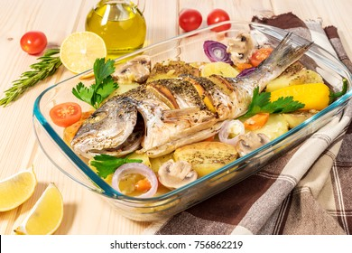 A delicious whole baked fish. Baked sea bream with lemon, onions, herbs, cherry tomatoes, spices and baked potatoes on a wooden background. Fried tasty fish. Diet and healthy food. Top view.