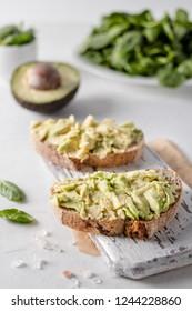 Delicious wholewheat toast with avocado slices. Close up fresh soft avocado toasts.