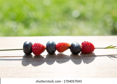Delicious wild strawberries and blueberries threaded on grass straw lying on wooden table in bright sunlight