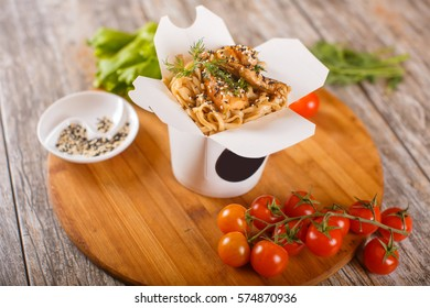 Delicious wok noodles box container with udon and chicken on wooden table. Chinese and asian takeaway fast food.