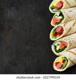 Delicious wrap tortillas with fresh healthy filling on rustic dark background.