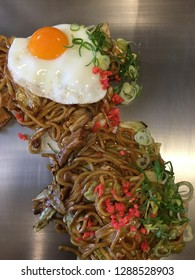 Delicious yakisoba, Japanese stir fry noodles, with egg and green onion, on a teppanyaki plate.