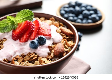 Delicious yogurt with granola and berries served on grey table, closeup