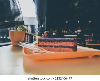 Delicious yummy yellow cake with chocolate on the table in cafe. Close up, shallow depth of the field, toned and processing photo.
