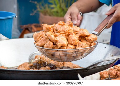 A delicious-looking spicy fried food or fried fish patty from a boiling pan of a roadside food stall in Thailand