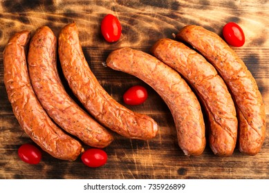 Deliciously smoked handmade Swedish Isterband sausages with natural casing. Here on burnt wooden cutting board with red tomatoes.