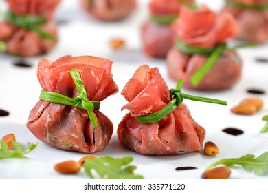 Delicoius air-dried beef ham - Italian Bresaola -  stuffed with chopped rocked salad, roasted pine nuts, parmesan cheese and creamy balsamic vinegar, tied up with blanched chives