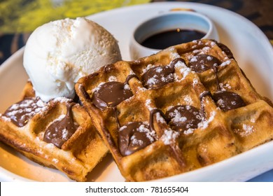 Delicous crispy waffle with ice-cream and chocolate syrup and caramel topping