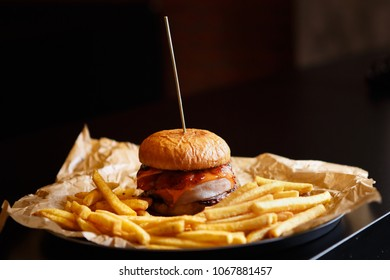 Delicous hamburger with beef meat cutlet served on plate in fast food restaurant.Big fat burger dish on table in cafe.Unhelathy,bad nutrition concept.Fastfood menu background