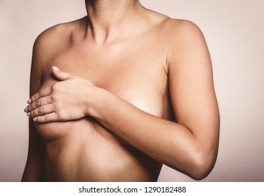 Delight view on woman bust covered by hand. Breast cancer concept.
