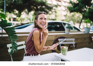 Delighted adult female in casual clothes holding tablet drinking green juice and laughing while having break in street cafe in summer