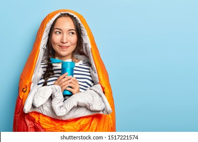 Delighted Asian female tourist holds flask with hot drink, wrapped in warm sleep bag, spends night in open air, has satisfied happy expression, natural beauty isolated on blue background. Rest concept