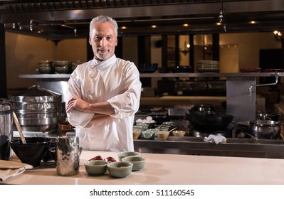 Delighted bearded chef standing in the kitchen of the restaurant