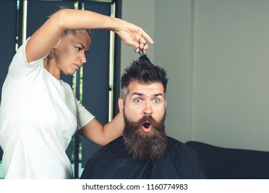 Delighted bearded male surprised while creating new form of his hairstyle. Time for new hairdo. Handsome young bearded man came to barber for haircut. hipster style. concept of fashion and beauty.