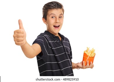 Delighted boy giving a thumb up and holding a bag of fries isolated on white background