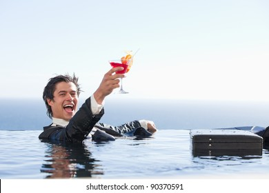 Delighted businessman relaxing in a swimming pool with a cocktail in a suit