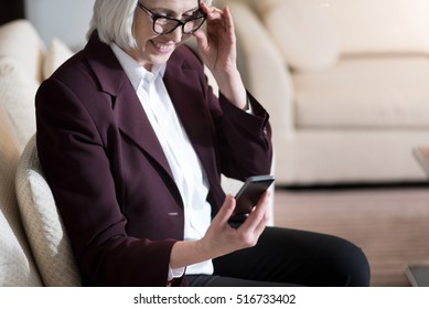 Delighted businesswoman holding the glasses and the mobile