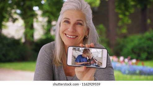 Delighted Caucasian grandmother plays video of grandkids playing with tablet