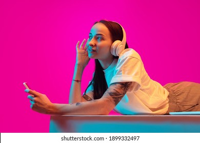 Delighted. Caucasian woman's portrait isolated on pink studio background in mixed neon light. Listening to music with phone. Concept of human emotions, facial expression, sales, ad, fashion. Copyspace