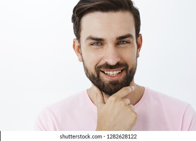 Delighted charming and charismatic bearded male with dark hair rubbing chin with satisfied intrigued smile posing interested and curious over gray background liking idea wanting fulfill it