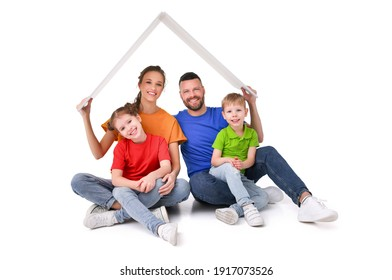 Delighted couple with kids sitting under paper roof in studio on white background while looking at camera and showing concept of relocation and new home