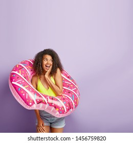 Delighted curly haired girl dreams about summer vacation, poses into rubber donut swim ring, shows her readiness for seasonal rest, wears casual outfit, isolated on violet wall. Holiday and swimming