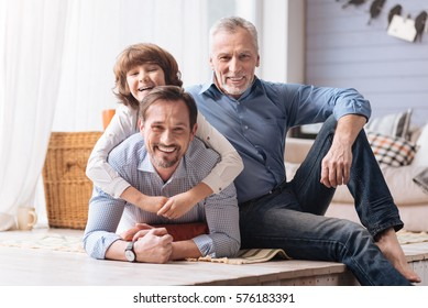 Delighted cute boy hugging his father