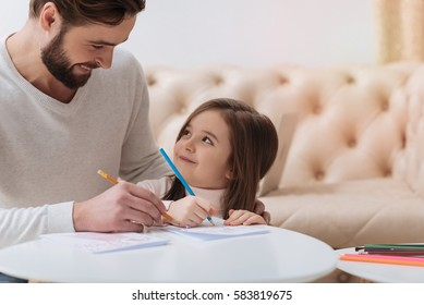 Delighted cute girl looking at her father