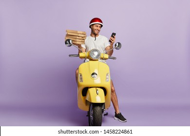 Delighted delivery man checks route via special application on mobile phone, holds paper containers with pizza, delivers fast food, wears protective helmet, rides yellow motorbike, isolated on purple