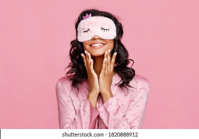 Delighted ethnic female in pajama and mask smiling and smearing lotion on face during skin care routine before sleep against pink background