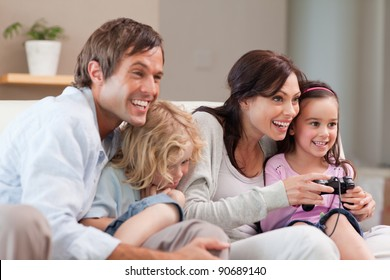 Delighted family playing video games together in a living room