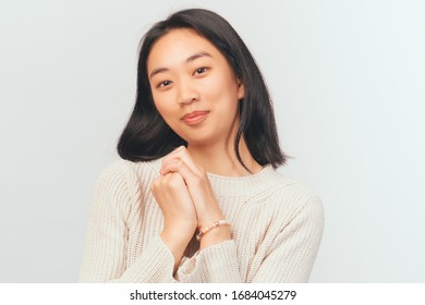 Delighted girl presses hands to face looking at camera. Beautiful young woman Asian appearance with black hair and brown eyes dressed in knitted warm sweater stands isolated white background in Studio