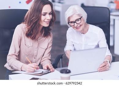 Delighted granny explaining details to her granddaughter