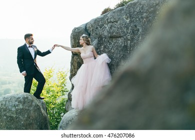 Delighted groom holding bride by the hand on the rock.