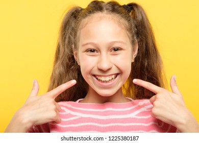 delighted happy joyous girl pointing to her smile. child dentistry and healthy teeth.