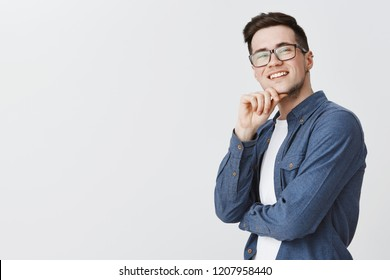Delighted happy and satisfied handsome young male student in glasses and blue shirt holding hand on chin and smiling being satisfied with idea coming to mind, standing pleased over grey wall