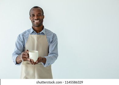 Delighted with the job. Cheerful afro americn barista drinking coffee against white background