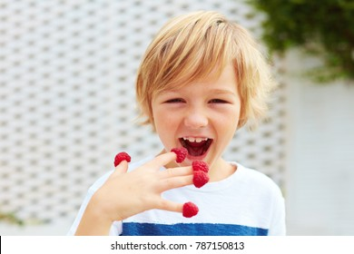 delighted kid, boy tasting ripe and fresh raspberries from his fingers