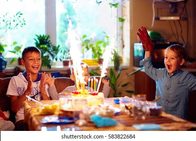 delighted kids blowing candles on cake, while celebrating a birthday party at home