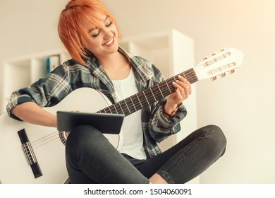 Delighted lady smiling and using tablet while sitting crossed legged and learning to play acoustic guitar in cozy home
