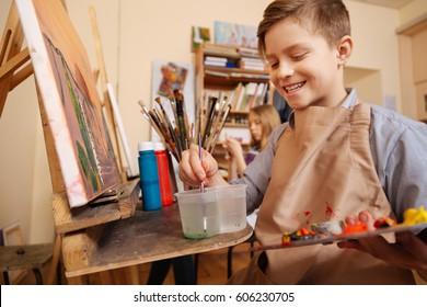Delighted little boy having art lesson at school