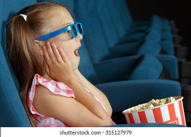 Delighted little girl watching film at the cinema