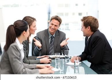 Delighted manager talking to his team at a table during a meeting