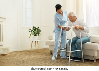 Delighted positive caregiver helping her patient