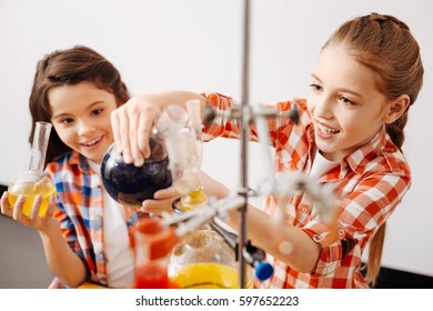 Delighted pretty girls enjoying their chemistry lesson
