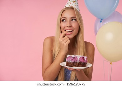 Delighted pretty woman rejoicing while posing in multicolored air balloons, celebrating birthday with delicious cake, looking aside positively and dreaming about future, isolated over pink background
