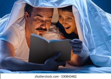 delighted Reading couple in bed