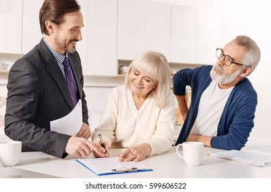Delighted real estate agent working with elderly couple of customers