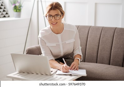 Delighted self employed woman writing in her notebook